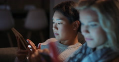 Friends using technology at home at night hanging out shopping online - stock footage