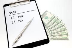 Clip board with ballot paper and dollar bills . Stock Photos