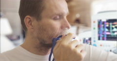 Young Man is Caughing Breathing Through Nebulizer Mask Parameters Displayed on Stock Footage