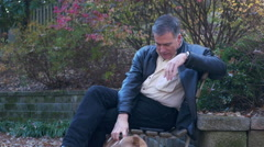 Man sitting on a park bench playing with his dog Stock Footage