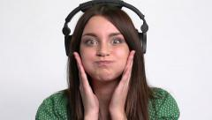 Young attractive girl listen music in professional headphones and grimacing. - stock footage