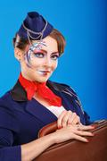 Stock Photo of Stewardess with face art baggage holds.