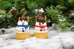 Decorated cupcake snowmen on snowy evergreen background Stock Photos