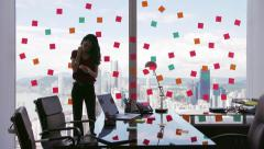 Business Person Attaching Sticky Notes On Large Window Stock Footage