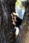 Young Woman Black Dress Sitting Between Tree Trunks - stock photo
