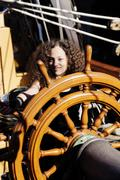 Stock Photo of Mixed Heritage Woman Standing At Steering Wheel Tall Ship