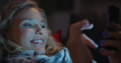 Beautiful blonde woman using smart phone technology at home at night Stock Footage
