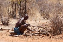 Himba man adjusts wooden souvenirs - stock photo