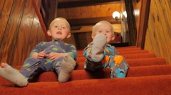 Baby brothers playing on the stairs Stock Footage