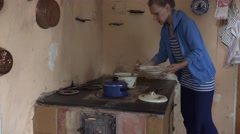 Wench woman take off cooked dumplings from boiling pot on retro stove. 4K Stock Footage