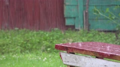 Heavy rain water drops fall and splash on wooden outdoor surface. 4K Stock Footage