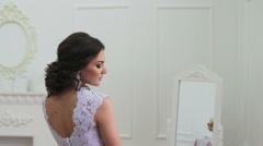 Beautiful young bride in stylish wedding gown standing near mirror Stock Footage