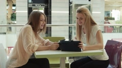 Two girls in intertainment center speaks and look in the tablet Stock Footage