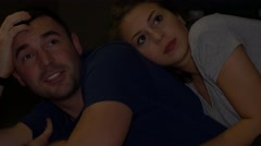 Young attractive couple cuddling watching TV - stock footage