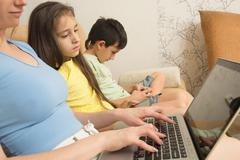 mother, daughter, son with laptop and tablet pc. Internet addiction - stock photo