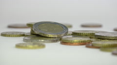 euro coins in a jumble and 1€ coin on the edge, white background - panoramic 1 - stock footage