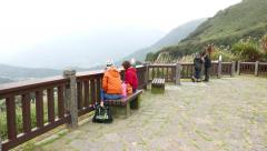 Observation area on corniche, tourists on bench look to foggy mountains land Stock Footage
