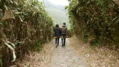 Young couple come down in green tunnel at high grass tangle, walk downstairs Stock Footage