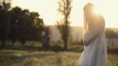 Tender pregnant woman with long hair wearing a transparent dress in the park  Stock Footage