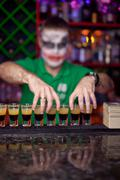 Bartender with make-up for Halloween proposes shot cocktail Stock Photos