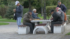 Elderly men playing chess in a park in Brasov Stock Footage