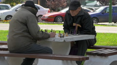 Two elderly men playing chess in a park in Brasov Stock Footage