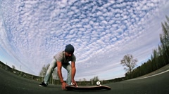 A young man is trying an olly jump with a skateboard on asphalt road. Fisheye Stock Footage