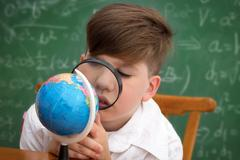 Schoolboy with loupe - stock photo