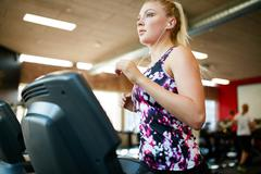 Fit woman running on treadmill in gym Stock Photos
