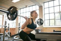 Female exercising in gym doing squats Kuvituskuvat