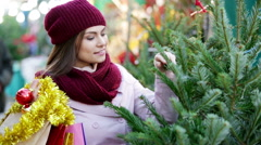 Happy woman   buying Christmas tree in market - stock footage