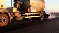 Oil spreader truck applying tack coats on a surface in preparation for paving - stock footage