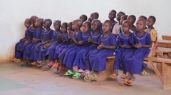 Maasai Mara school children in classroom singing and clapping Stock Footage