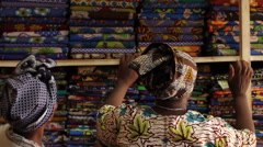 African lady in traditional clothing in fabric shop looking at fabric Stock Footage