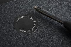 closeup of screwdriver and warranty seal - stock photo
