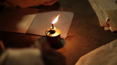 African child doing homework infront of kerosene lamp - stock footage