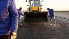 Workers applying reinforcement mesh on a surface in preparation for paving - stock footage