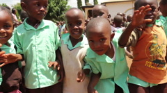 Group of young African children wave at camera smiling and happy Stock Footage