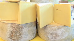 Stock Video Footage of Cheese wheels stacked on the marketplace