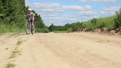 Boy rides a bicycle near the field on the sand road in a farm Stock Footage