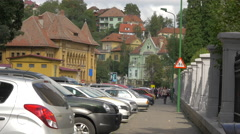Cars parked on a street with old buildings in Brasov Stock Footage