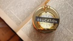 Inscription education, textbook and gold pocket watch Stock Footage