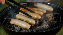 Bratwurst sausages cooking on a barbecue Stock Footage