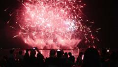 people sitting at beach and watching fireworks - stock footage