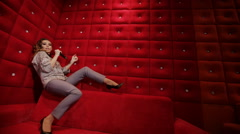 Elegant girl with a microphone singing karaokeof a red sofa on a red background Stock Footage