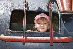 Little girl inside a welded metal attraction - stock photo