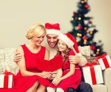 Stock Photo of smiling family reading postcard