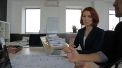 Two beautiful young businessman talking on the project, which lies in front of Stock Footage