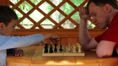 Boy playing chess, makes a move, son with father playing chess Stock Footage
