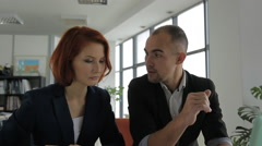 A middle-aged man businessman business manager talking with his client, woman in Stock Footage